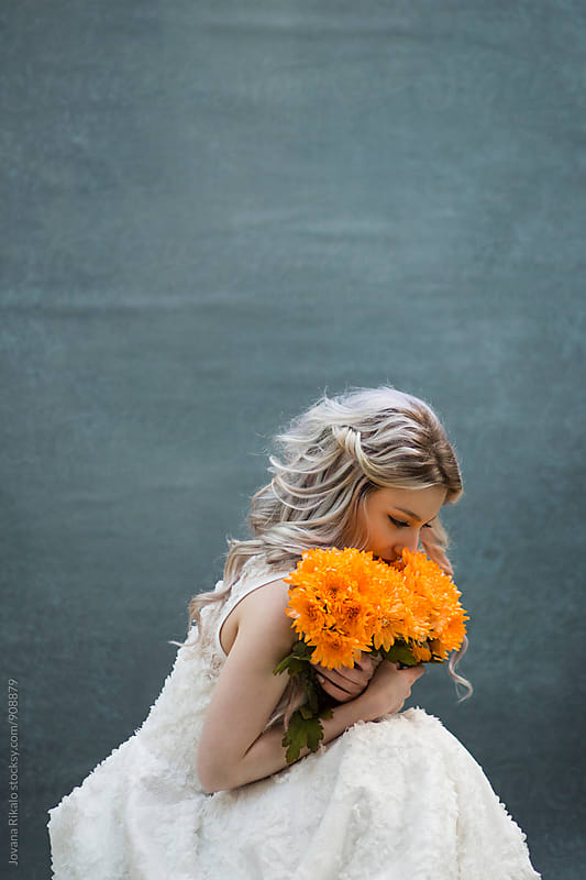 Young woman in a white dress holding flower bouquet by Jovana Rikalo for Stocksy United