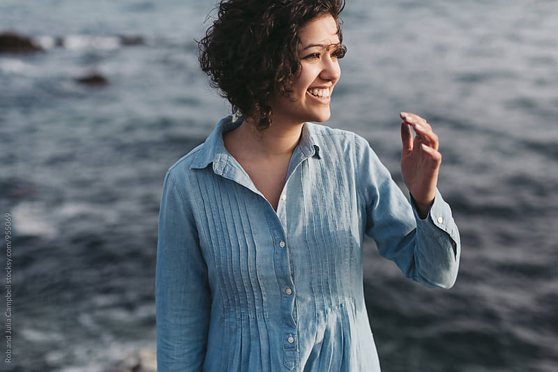 Portrait of young happy woman hanging out in near ocean by Rob and Julia Campbell for Stocksy United