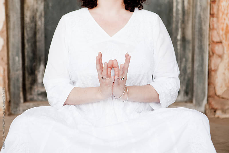 Woman doing yoga mudra by Christine Love Hewitt for Stocksy United