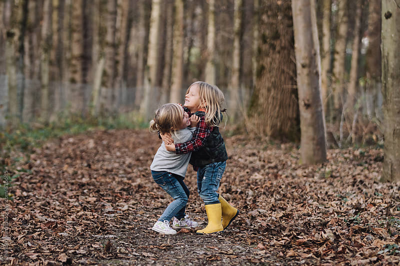 little boy and girl scrambling in autumnal forest by Leander Nardin for Stocksy United