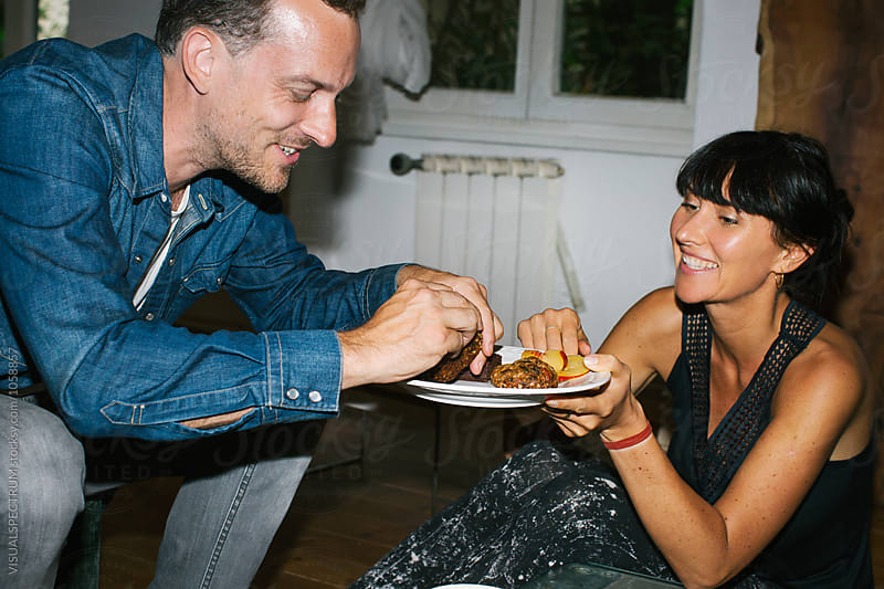 Snapshot of Pretty Smiling Caucasian Woman Offering Brownies and Sliced Peach to Male Guest at Casual Dinner Party by Julien L. Balmer for Stocksy United