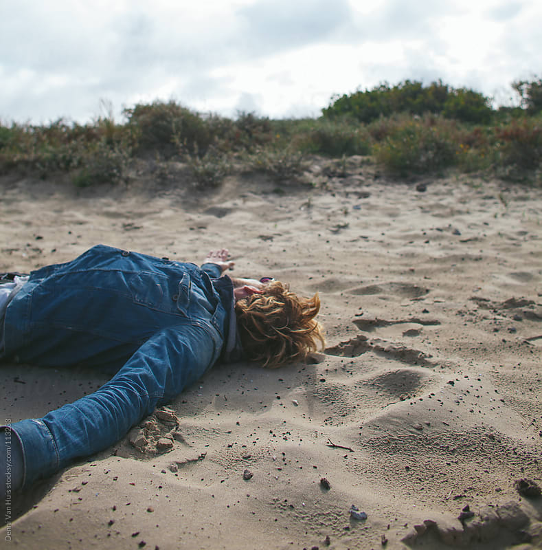 Man laying in the sand. by Denni Van Huis for Stocksy United