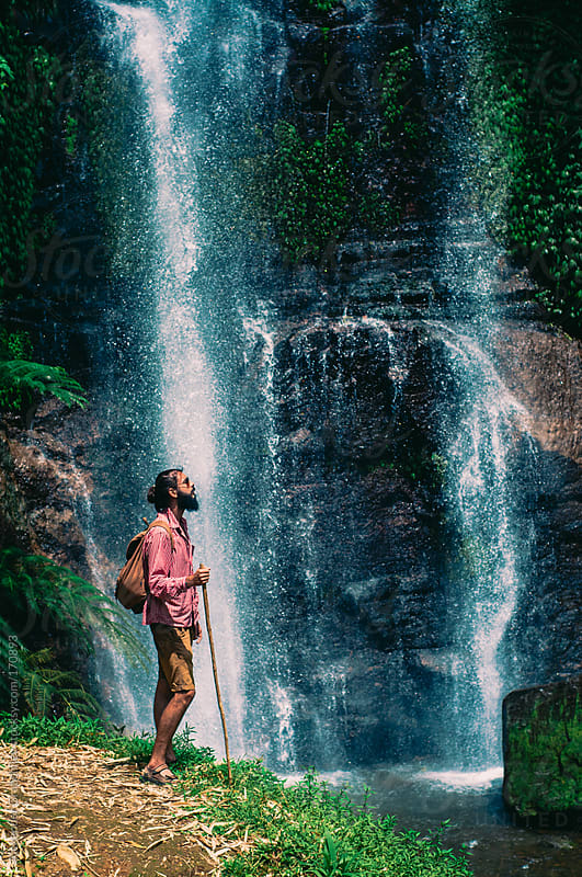 Young man with walking stick standing in front of the waterfall by Alexander Grabchilev for Stocksy United