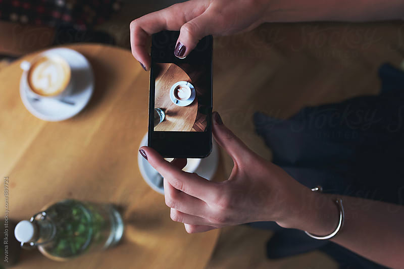 Young woman taking photo of a coffee by Jovana Rikalo for Stocksy United