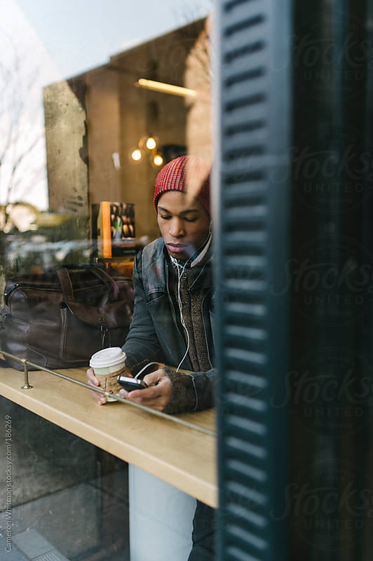 Stylish black man drinking coffee in a shop by Cameron Whitman for Stocksy United