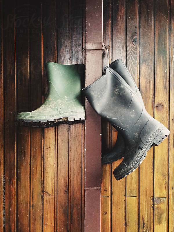 Two Pairs of Rain Boots Hanged by the Gutter on the Wooden Wall by Nemanja Glumac for Stocksy United