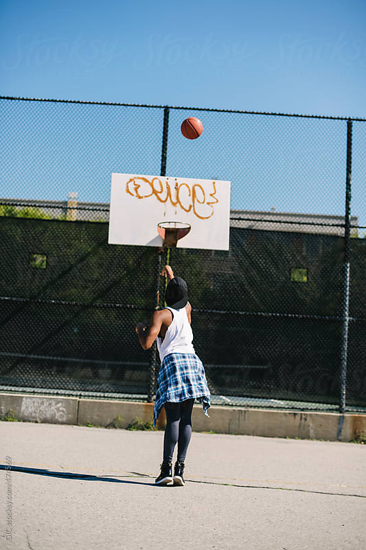 Young woman playing basketball outdoors in urban area by GIC for Stocksy United