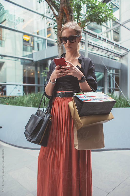 Stylish woman texting on her phone, and holding her shopping bags outside a large shopping mall by Jovo Jovanovic for Stocksy United