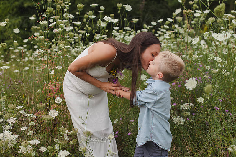 A pregnant mother bending down to kiss her young son by Amanda Worrall for Stocksy United