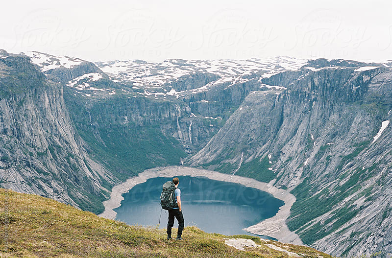 A young hiker with backpack on his way to Trolltunga in Norway by Atle Rønningen for Stocksy United