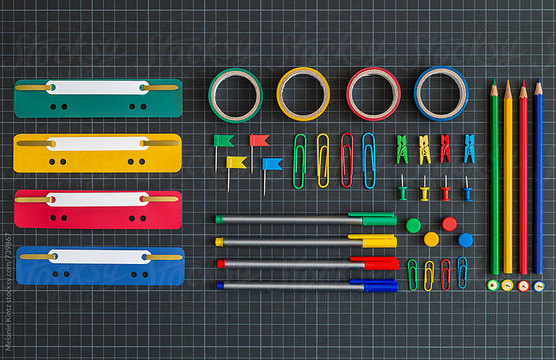 Multicolored office tools on dark background by Melanie Kintz for Stocksy United