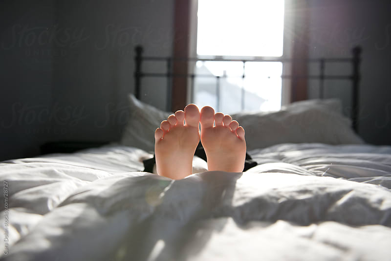 Kid feet laying down on the bed by Cara Dolan for Stocksy United