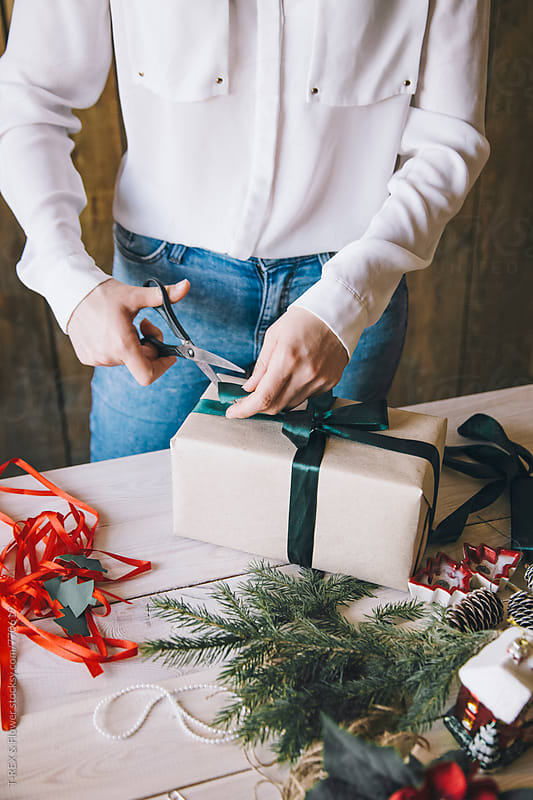Woman decorating Christmas gift with teal ribbon by Danil Nevsky for Stocksy United