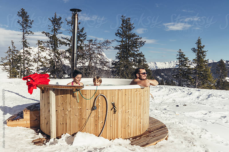 young family sitting in outdoor jacuzzi in snowcovered winter landscape by Leander Nardin for Stocksy United
