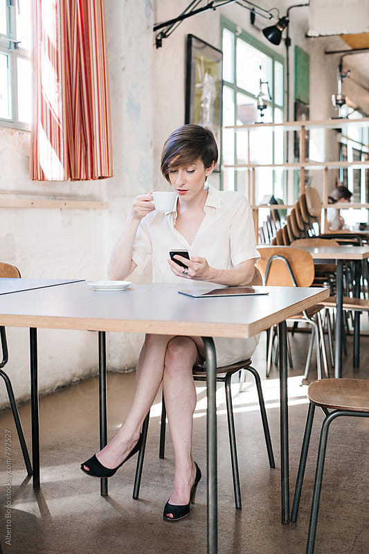 Young woman using her mobile phone. by Alberto Bogo for Stocksy United