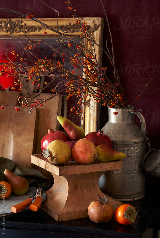 A dark, warm-toned still life with persimmons, wood pedestal, bowls, framed mirrors by Sherry Heck for Stocksy United