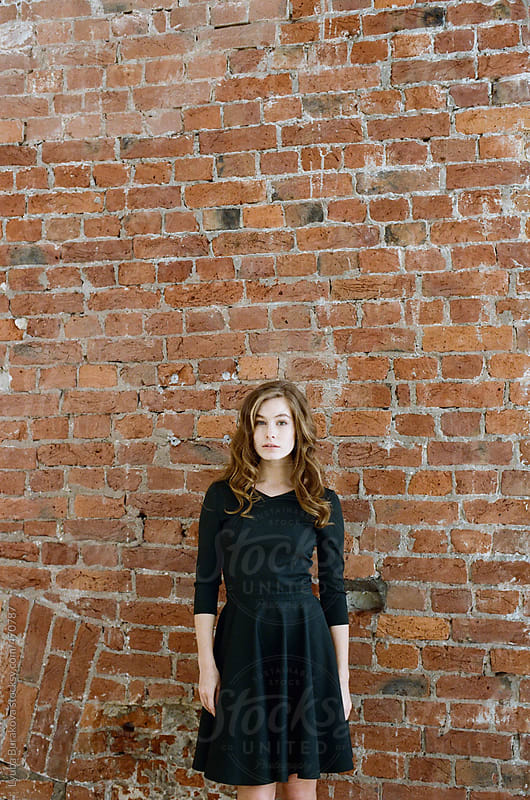 Young woman standing in front of brick wall by Lyuba Burakova for Stocksy United