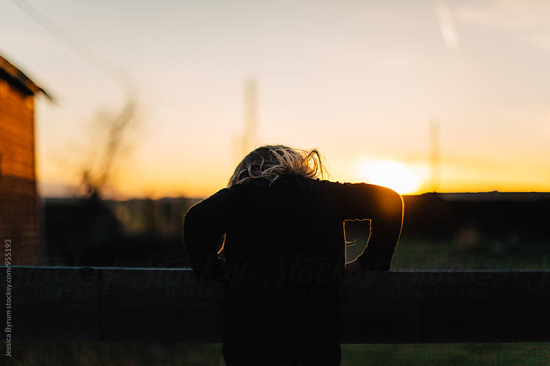 Small child on fence at sunset by Jessica Byrum for Stocksy United
