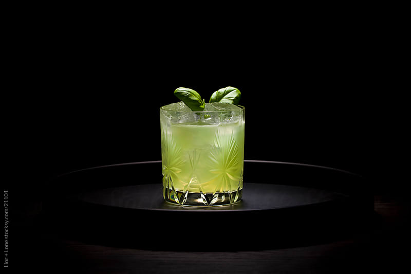 Green cocktail on round dark tray by Lior + Lone for Stocksy United