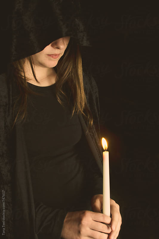 young woman in black holds lighted candle by Tana Teel for Stocksy United