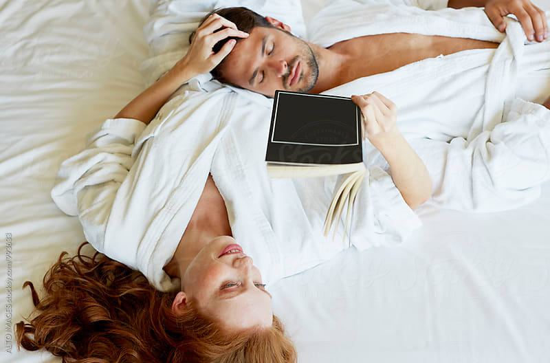 Woman Reading Book While Man Sleeping In Bedroom by ALTO IMAGES for Stocksy United