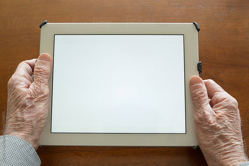 POV of a senior adult man using a digital tablet by David Smart for Stocksy United