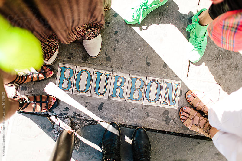 A group of people standing around the words Bourbon on the street.  by Kristen Curette Hines for Stocksy United