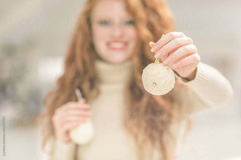 Smiling Woman Holding Christmas Ornaments by Lumina for Stocksy United