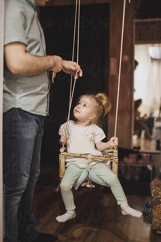 Little girl on the hand made swing at home looking at her dad by Irina Efremova for Stocksy United
