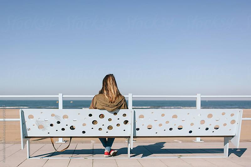 Girl sitting on a bench enjoying the view of the ocean. by Koen Meershoek for Stocksy United
