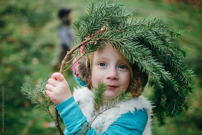 Portrait of a Little Girl, Framed by Pine Needles by Amanda Voelker for Stocksy United