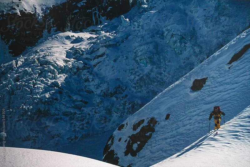 Skier hiking in snow above blue ice glacier in Chamonix, France by Soren Egeberg for Stocksy United