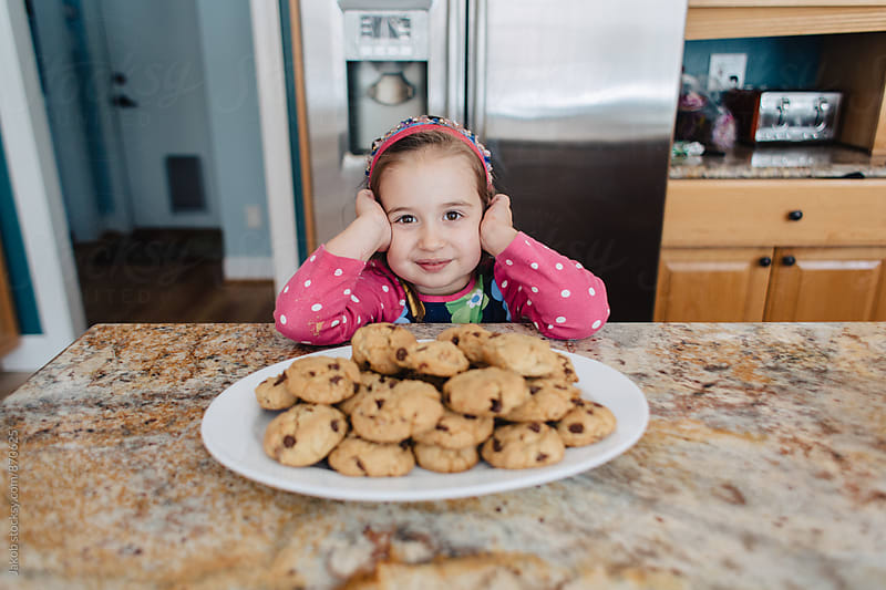 Excited young girl standing in front of a tray of chocolate chip cookies by Jakob for Stocksy United