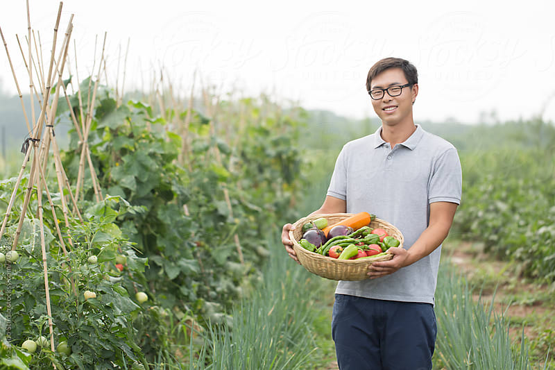 Young Chinese farmer holding vegetable grown on farm by Maa Hoo for Stocksy United