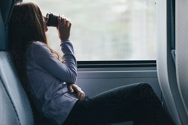Young anonymous woman drinking coffee looking through train window by Ilya for Stocksy United