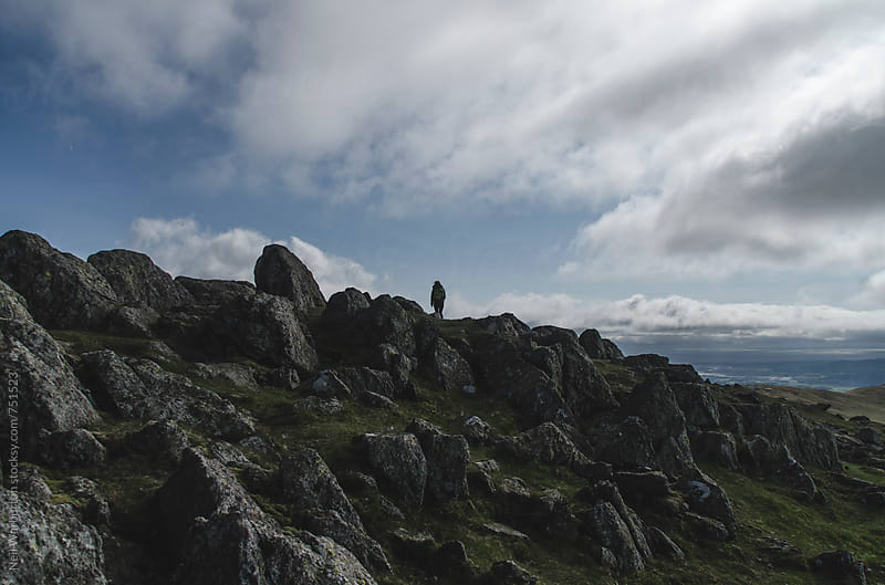 A lone hiker crossing rocky terrain by Neil Warburton for Stocksy United