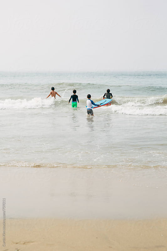 Young boys playing in the ocean catching waves by Curtis Kim for Stocksy United