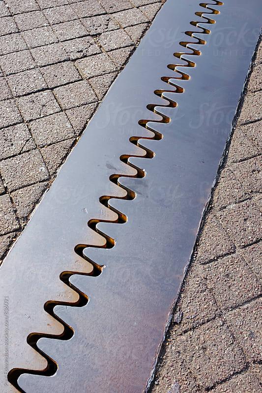 Detail of joined metal plates on urban sidewalk by Paul Edmondson for Stocksy United