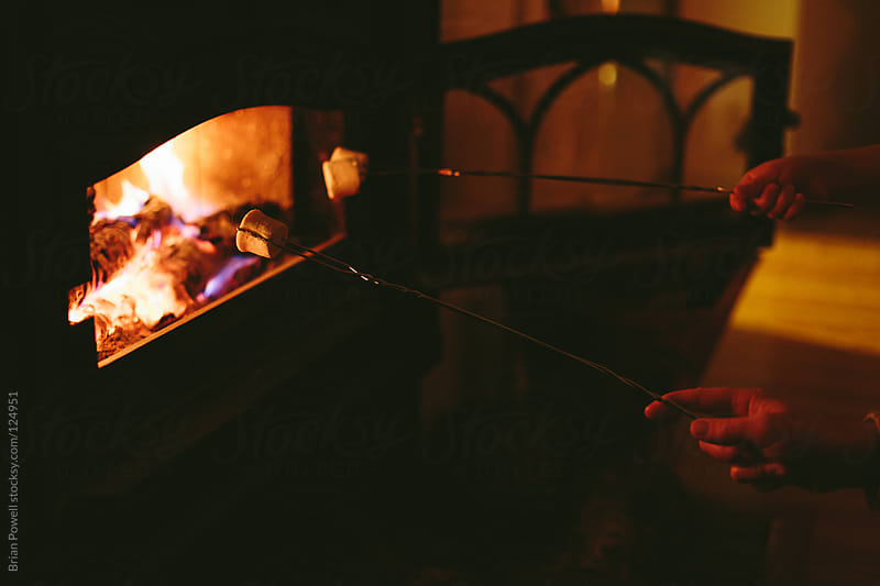roasting marshmallows in the wood stove by Brian Powell for Stocksy United