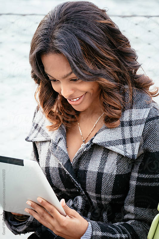 Woman working on a digital tablet outdoors by Good Vibrations Images for Stocksy United