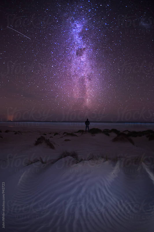Man looking up at the Milky Way. by John White for Stocksy United