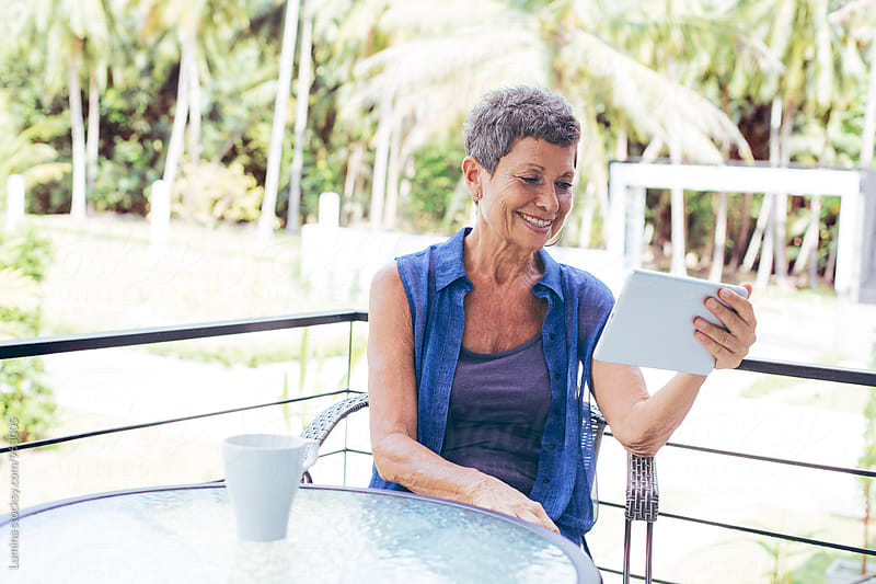 Senior Woman Using a Tablet on the Balcony at Home by Lumina for Stocksy United