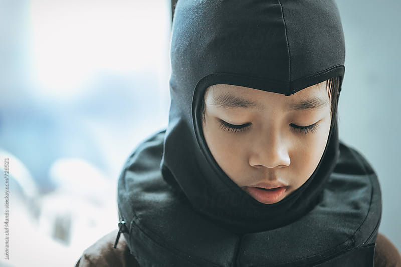 Young kid wearing balaclava mask in deep thought during lull of karting practice by Lawrence del Mundo for Stocksy United