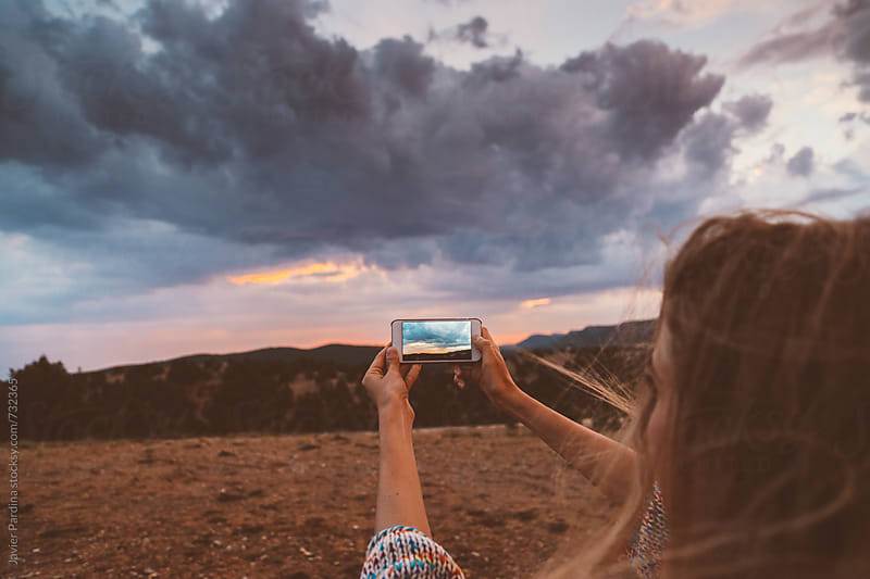 woman are doing photos from sunset with smartphone by Javier Pardina for Stocksy United