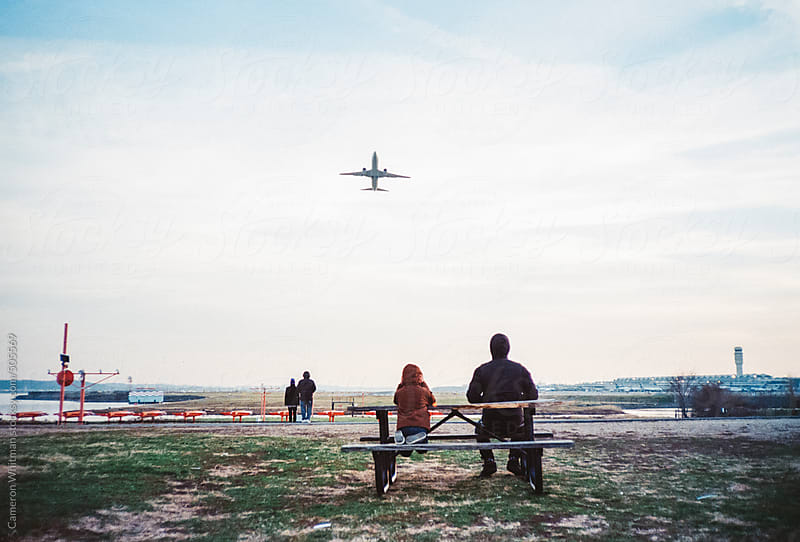 Young boy and his uncle watching airplanes take off  by Cameron Whitman for Stocksy United