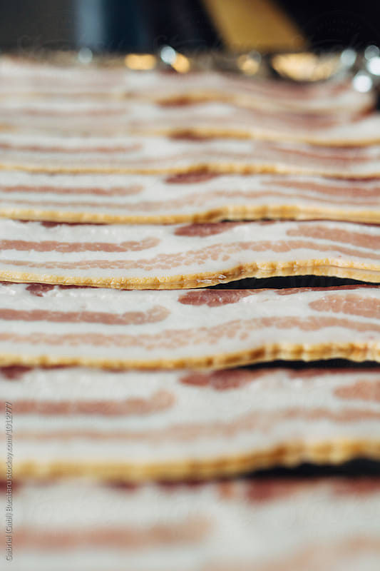 Uncooked bacon in a tray by Gabriel (Gabi) Bucataru for Stocksy United