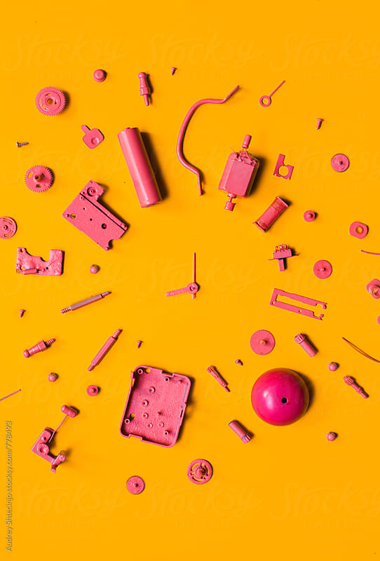 Organised Disassembled Clock/pink parts on orange background by Marko Milanovic for Stocksy United