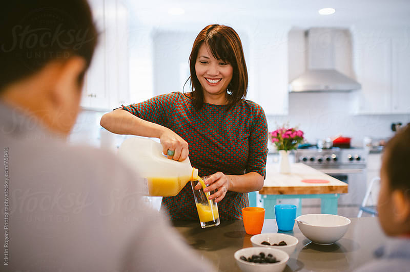 Mother smiles at family while pouring orange juice in kitchen by Kristin Rogers Photography for Stocksy United