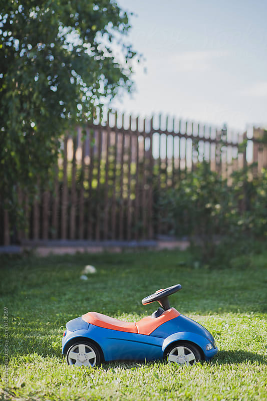 Blue and orange kids car standing on the grass by Irina Efremova for Stocksy United