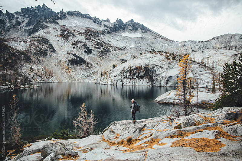 Hiker with camera enjoys wild landscape by Tari Gunstone for Stocksy United